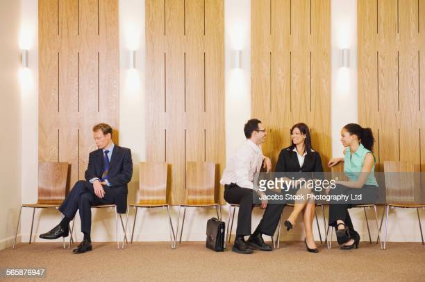 Business people ignoring businessman in waiting area