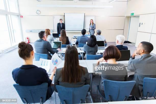 mensen uit het bedrijfsleven in een klaslokaal luisteren docenten - theaterzaal stockfoto's en -beelden
