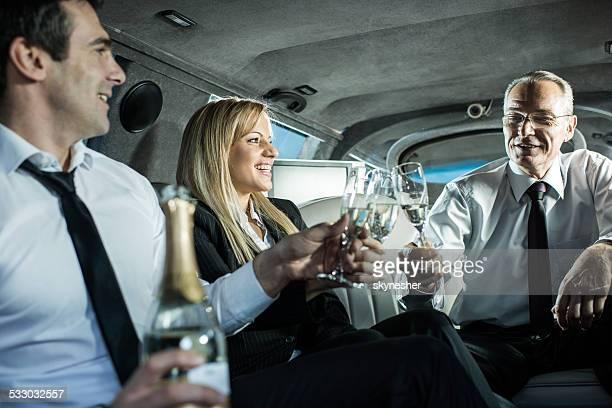 Gens d'affaires dans une limousine avec un toast au champagne.
