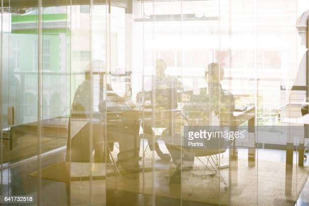 business people in board room seen through glass - photographed through window stock pictures, royalty-free photos & images