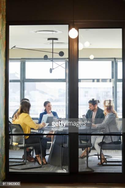 Geschäftsleute im Sitzungsraum durch Glas gesehen