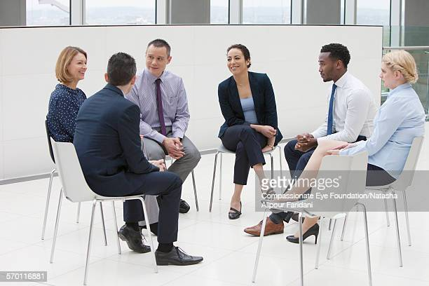 Business people in circle of chairs