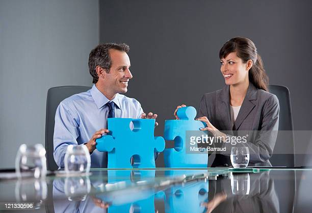 Business people in conference room with jigsaw puzzle pieces
