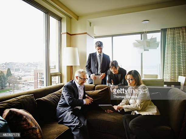 business people in discussion in hotel room suite - leanintogether stock pictures, royalty-free photos & images