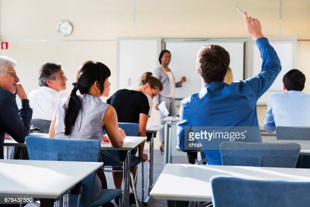 Business people in education room listening lecture of cute black teacher from Cuba