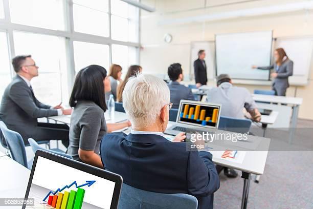 Geschäftsleute in Bildung Zimmer hören Vortrag von ältere Lehrer