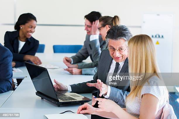 Business people in education room working and talking about problems