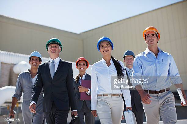 Business people in hard-hats walking together outdoors