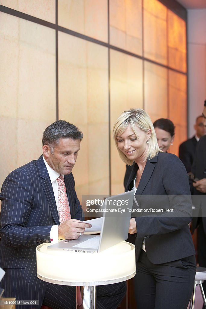 Business people in hotel lobby in front of laptop : Stock Photo