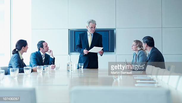business people in meeting in conference room - mid adult men stock pictures, royalty-free photos & images