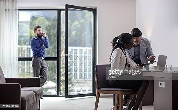 Business people in meeting in hotel room suite