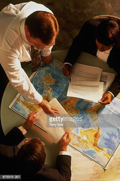 Business people in meeting, map on table