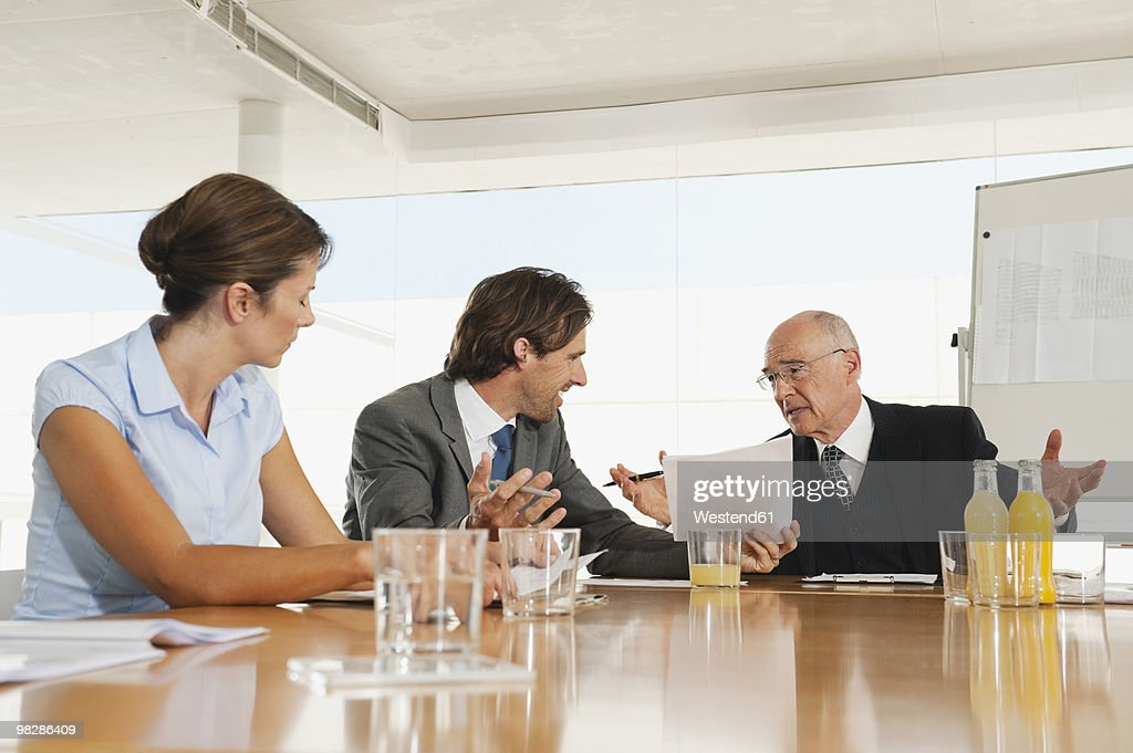 business people at conference table man making hand gestures