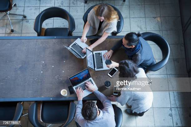 Business people in office meeting using laptops
