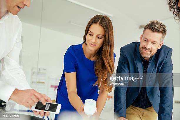 Business people in office using smartphone and wifi power socket