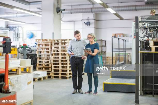 Business people in printing house using digital tablet