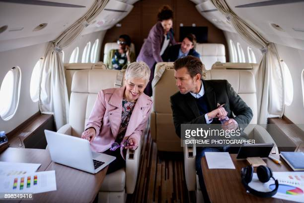 mensen uit het bedrijfsleven in prive-jet vliegtuig - voertuiginterieur stockfoto's en -beelden