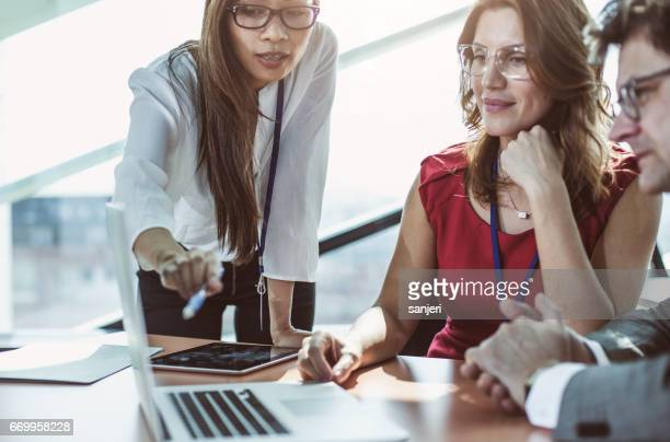 Business People in the Board Room Discussing, Using Laptop
