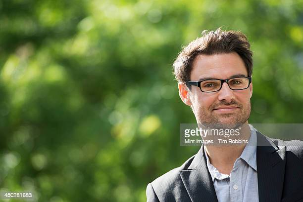 Business people in the city. Keeping in touch on the move. A man with short dark hair and glasses. Smiling at the camera.