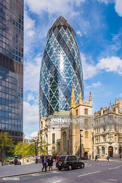 Business people in the City of London with the Swiss Re Building aka Gherkin in the background