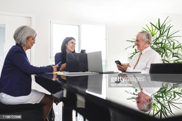 business people in the office - sentar se imagens e fotografias de stock
