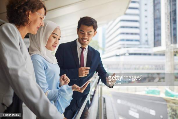 business people in the streets of kuala lumpur on the move. - kuala lumpur stock pictures, royalty-free photos & images