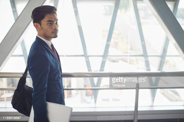 business people in the streets of kuala lumpur on the move. - monorail stock pictures, royalty-free photos & images