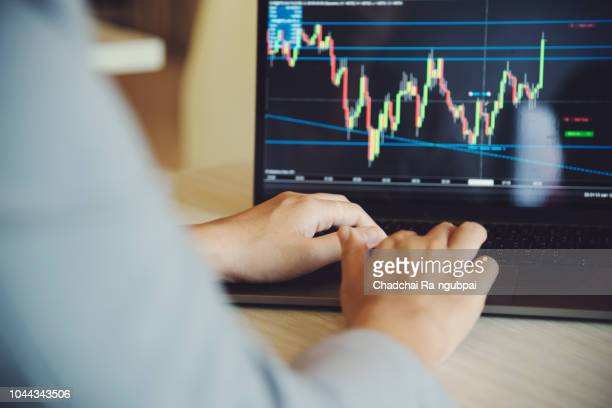 Business people is analyzing the financial graph and graph of the FOREX, Businessman are pointing to profitable investments in the foreign exchange market or FOREX.