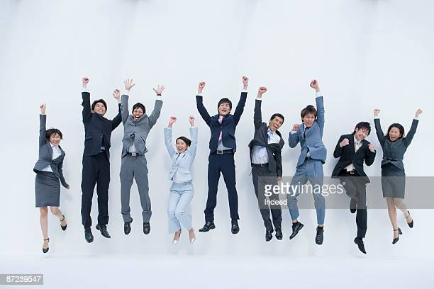 Business people jumping and clenching fists