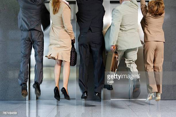 Business People Jumping in Front of Elevator