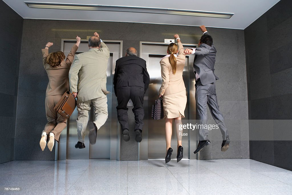 Business People Jumping in Front of Elevator : Stock Photo