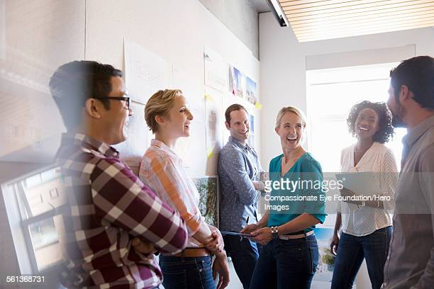 business people laughing in meeting - groupe moyen de personnes photos et images de collection