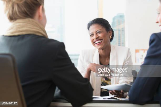 Business people laughing in office meeting