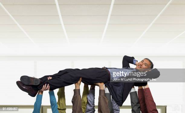Business people lifting Chinese businessman overhead