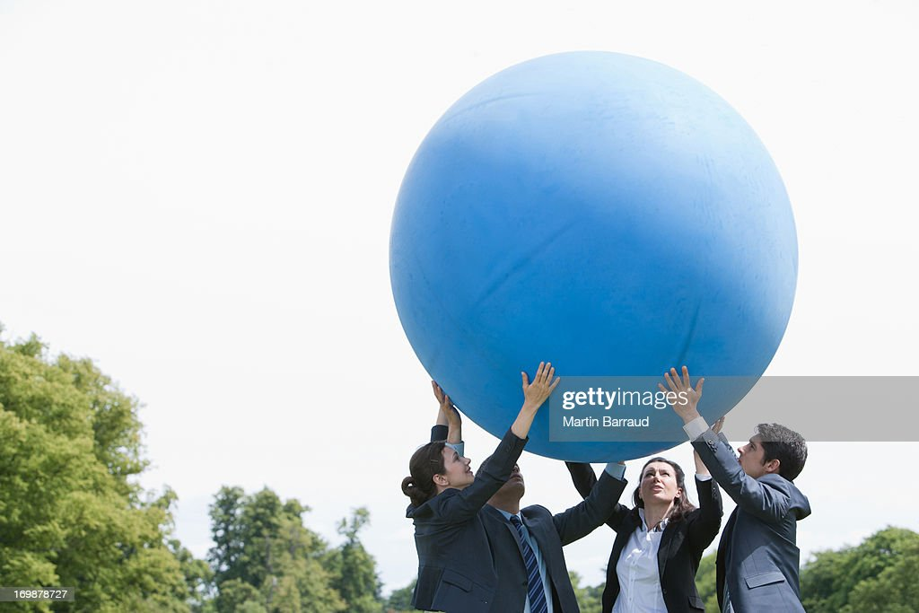 Business people lifting large ball together : Stock Photo