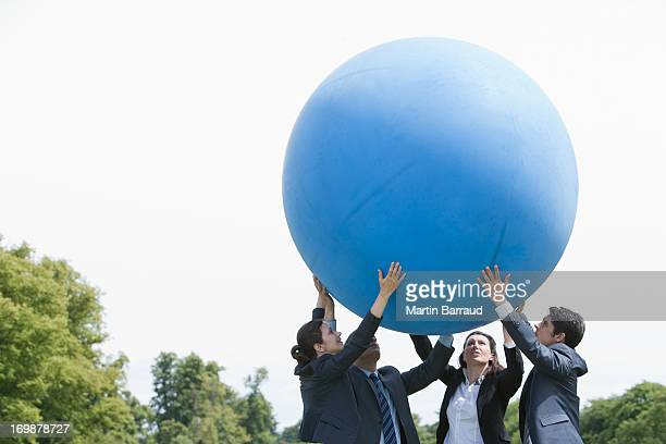 Business people lifting large ball together