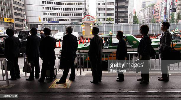 Business people line up to take taxi at a station in Tokyo Japan on Tuesday May 15 2007 Japan's jobless rate unexpectedly fell to a nineyear low in...