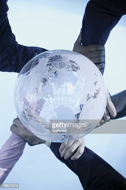 Business people linking arms with globe above them