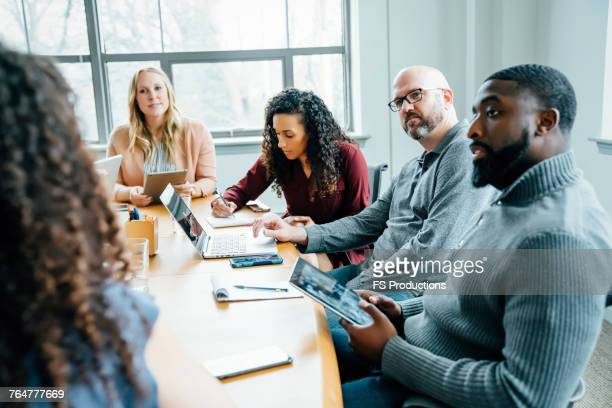 business people listening in meeting - multiculturalism stock pictures, royalty-free photos & images