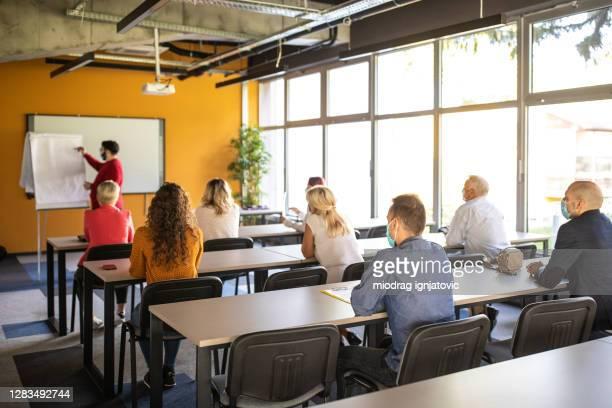 uomini d'affari che ascoltano il presentatore durante la conferenza aziendale nel centro congressi - concorso foto e immagini stock