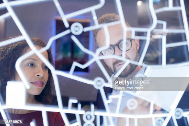 business people looking at a futurisitic digitally generated display - direction - fotografias e filmes do acervo