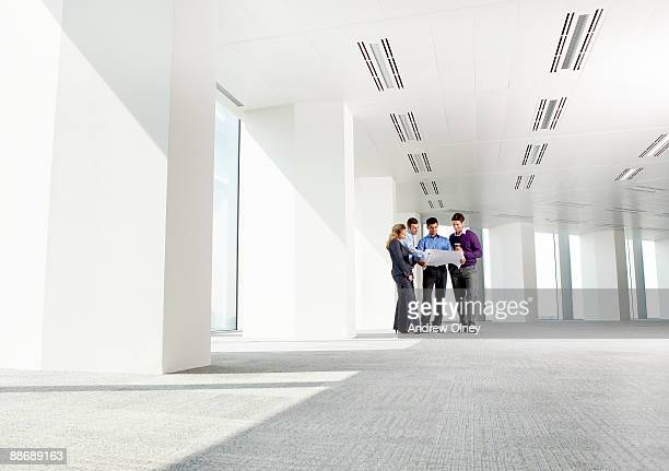Business people looking at blueprints in empty office