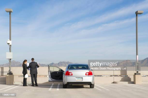 Business people looking at blueprints in parking lot