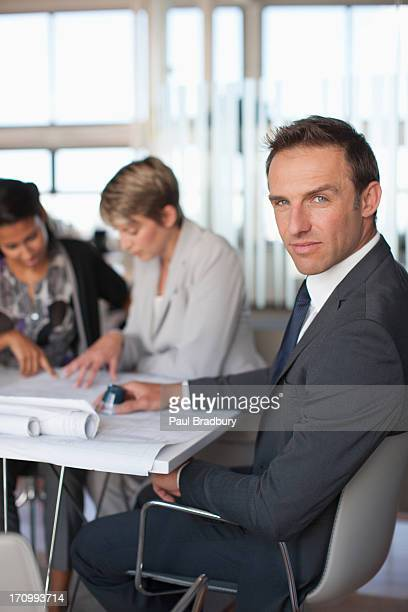 Business people looking at blueprints together