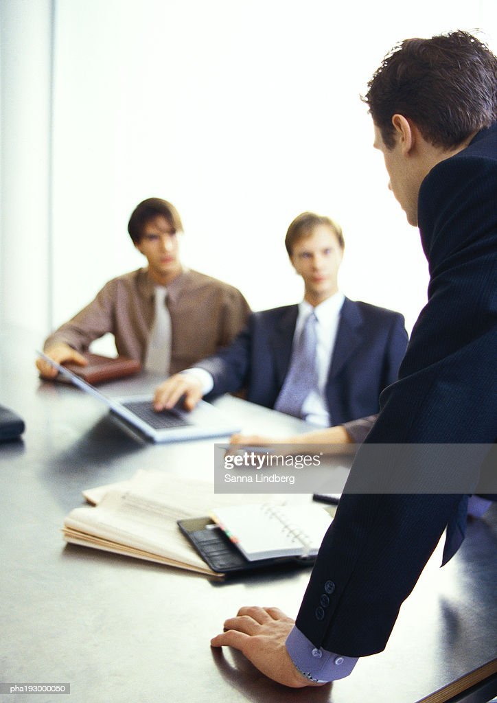 Business people looking at businessman standing. : Stockfoto