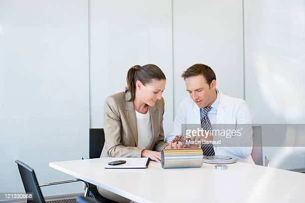 Business people looking at circuit board together in conference room