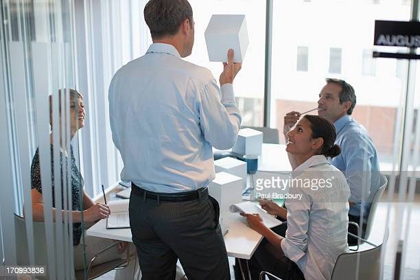 Business people looking at cubes in conference room