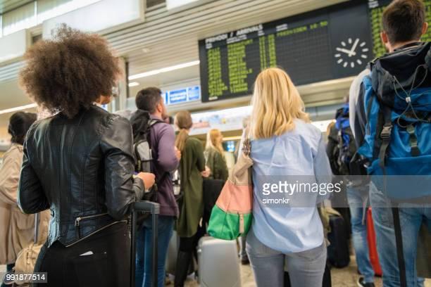business people looking at departure board - mid adult men imagens e fotografias de stock