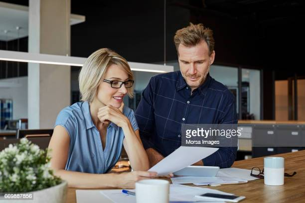 Business people looking at document at desk
