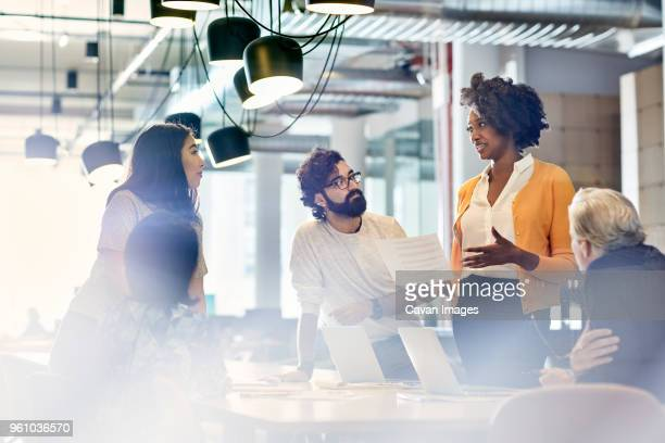 business people looking at female colleague explaining documents while standing at conference table - business plan stock pictures, royalty-free photos & images